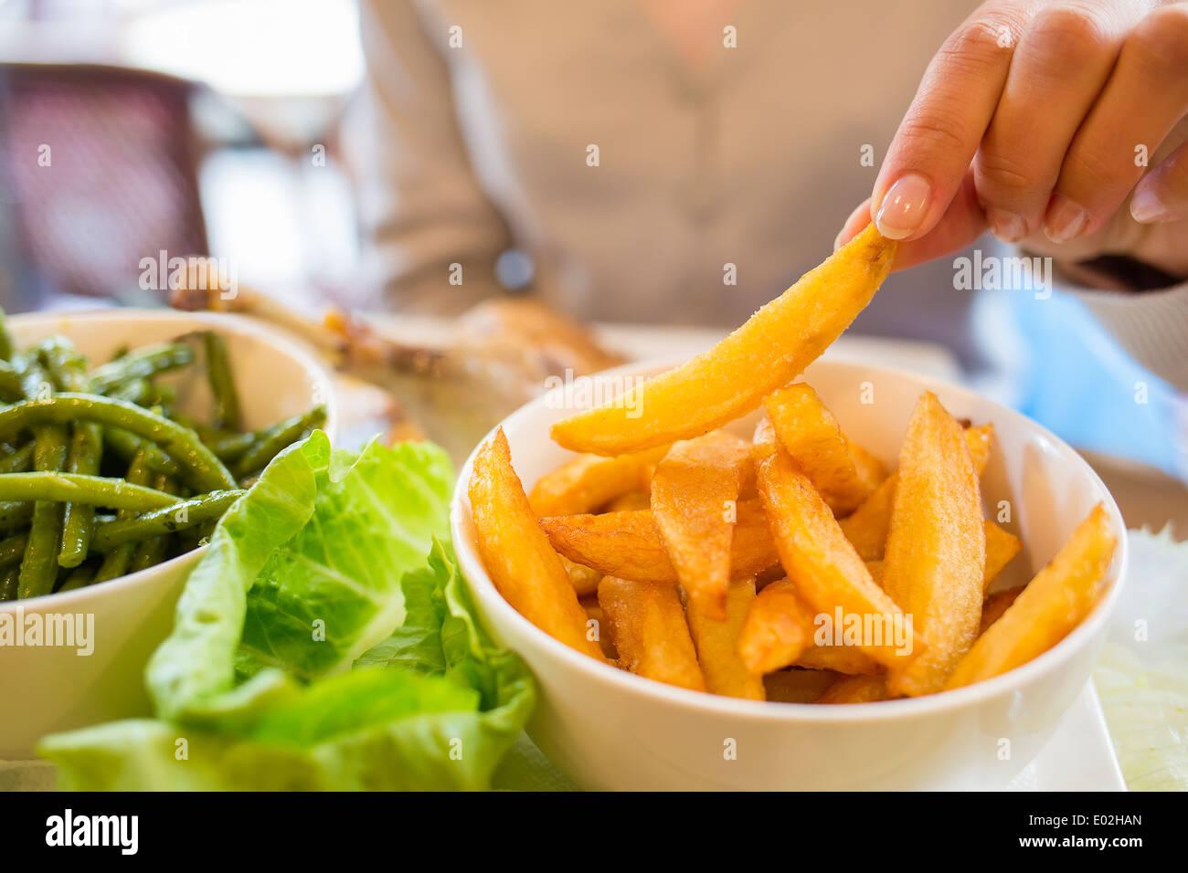 Female eating meat close-up finger bar indoor - Stock Image
