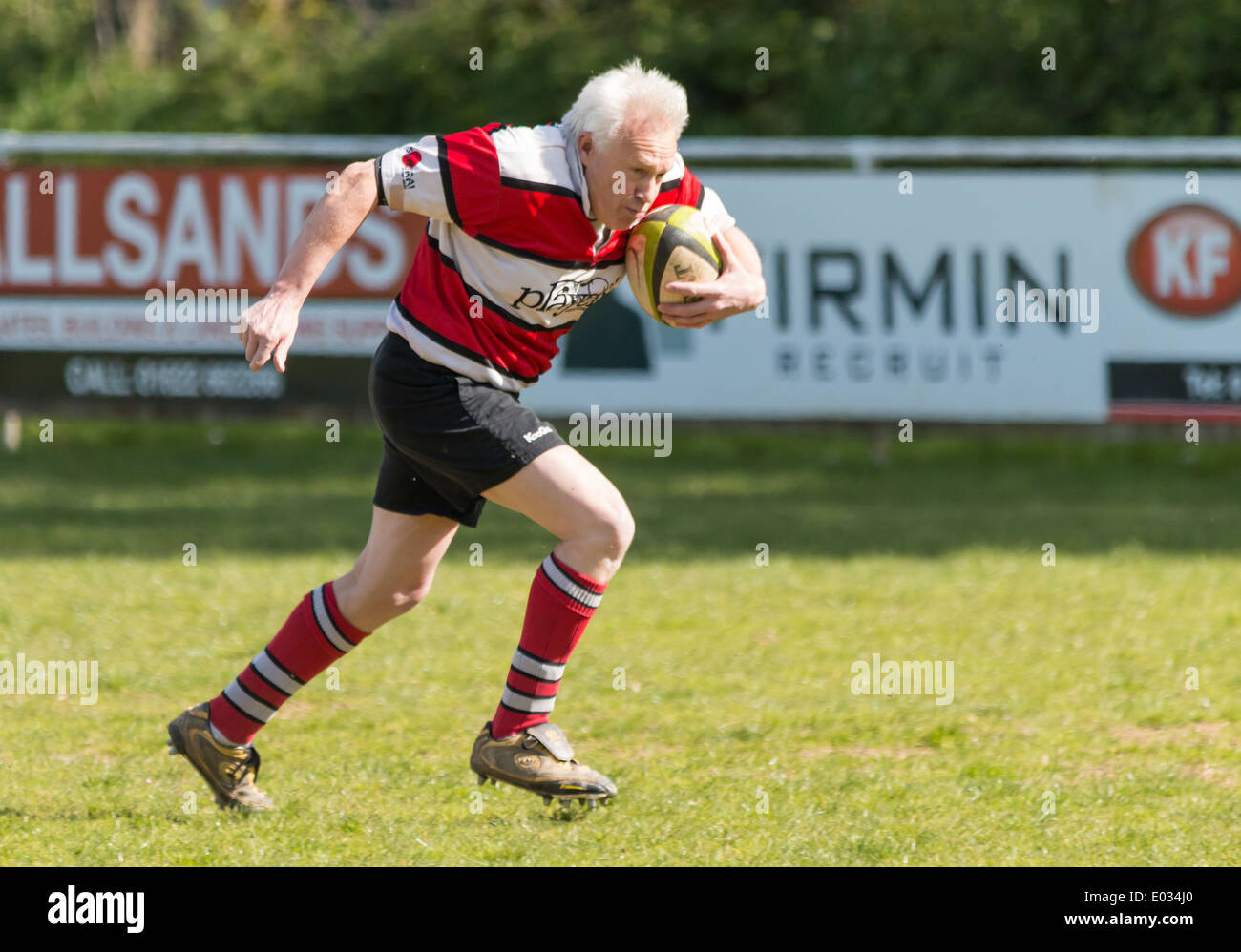 Mature Rugby Player Running with Ball - Stock Image