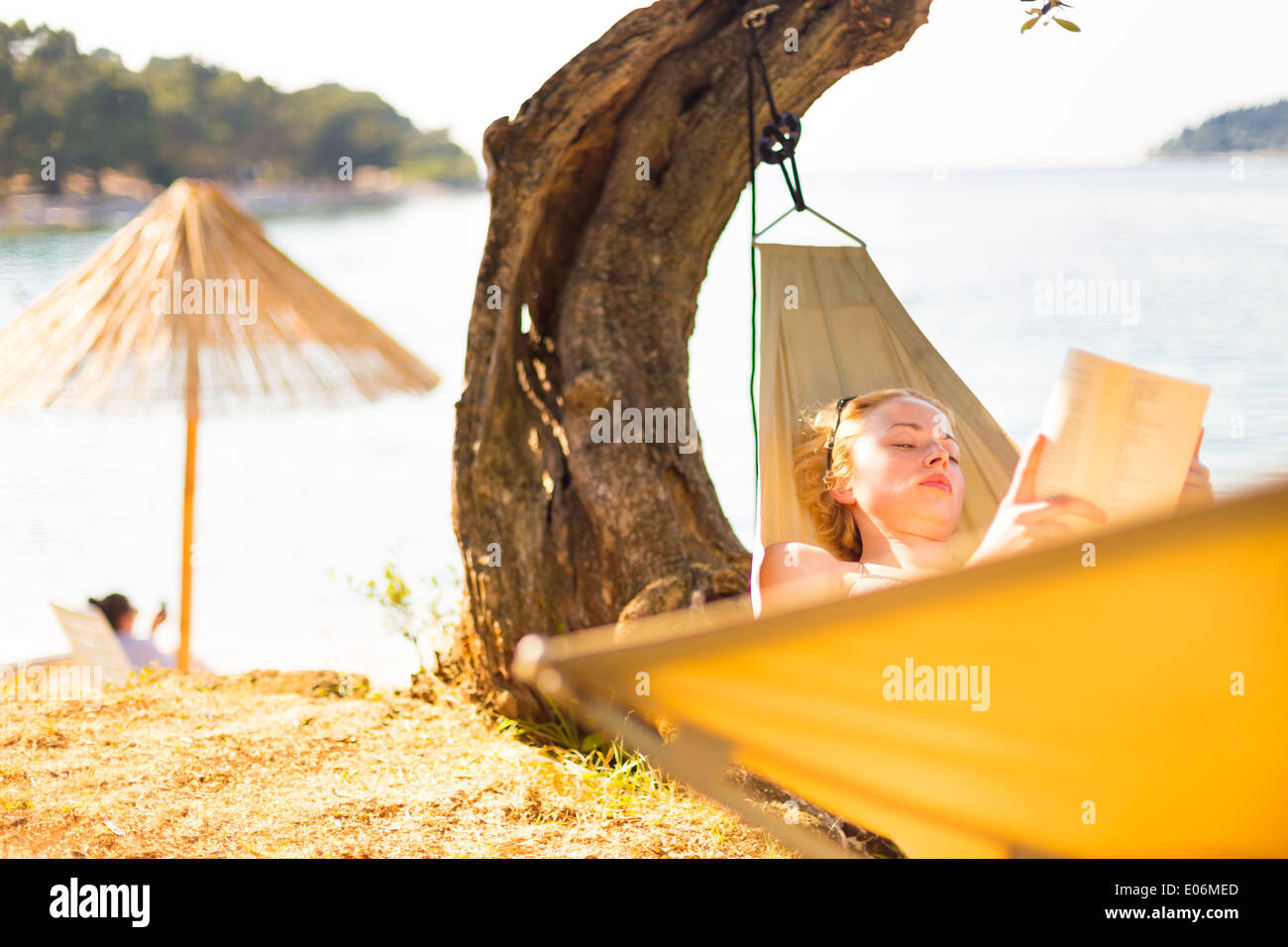 Lady reading book in hammock. - Stock Image