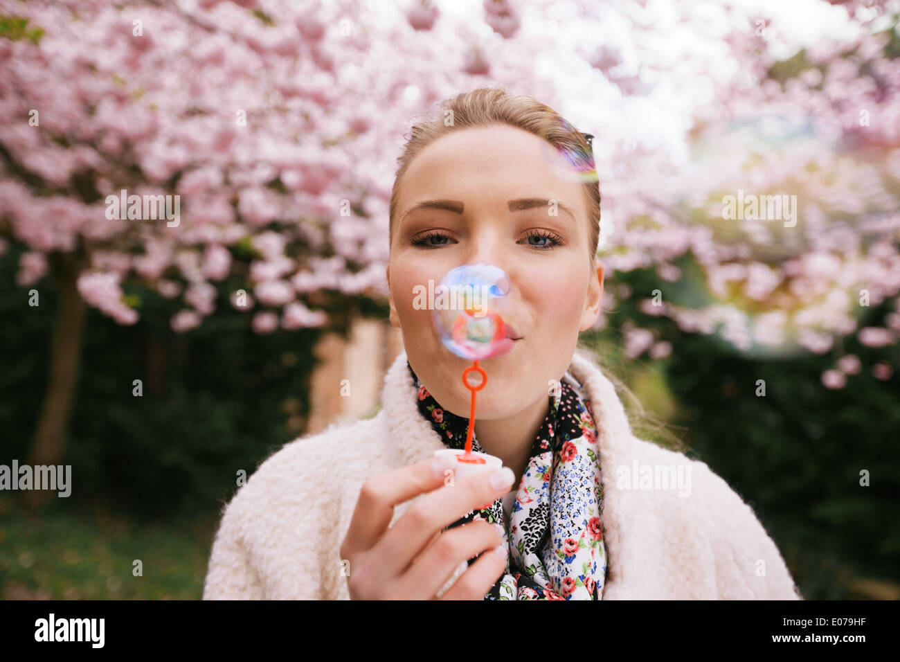 Portrait of beautiful young woman blowing bubbles at park. Pretty female model with bubble wand at spring blossom - Stock Image