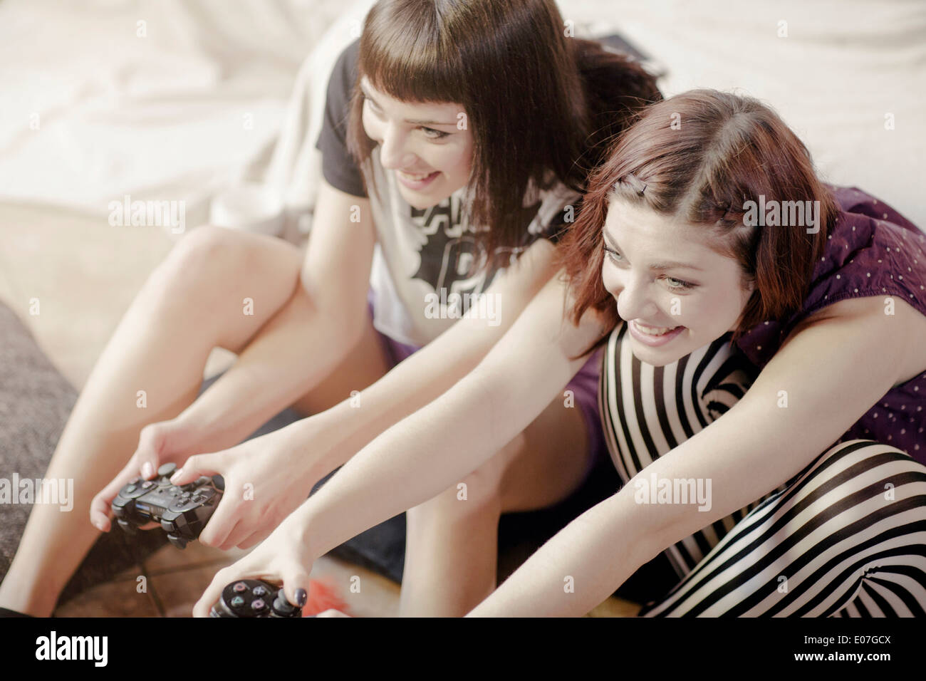 Two young women playing video games - Stock Image