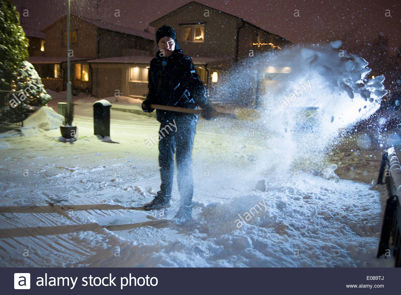 Full length of man removing snow from street - Stock Image