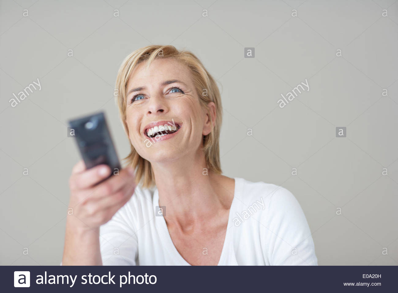 Mature woman holding remote control - Stock Image