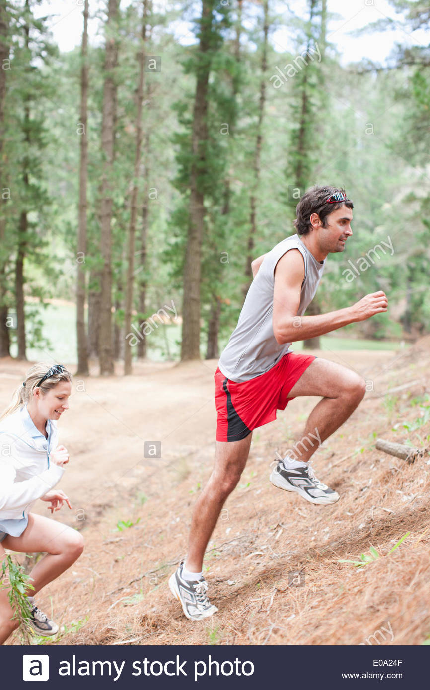 Couple climbing hill in forest - Stock Image