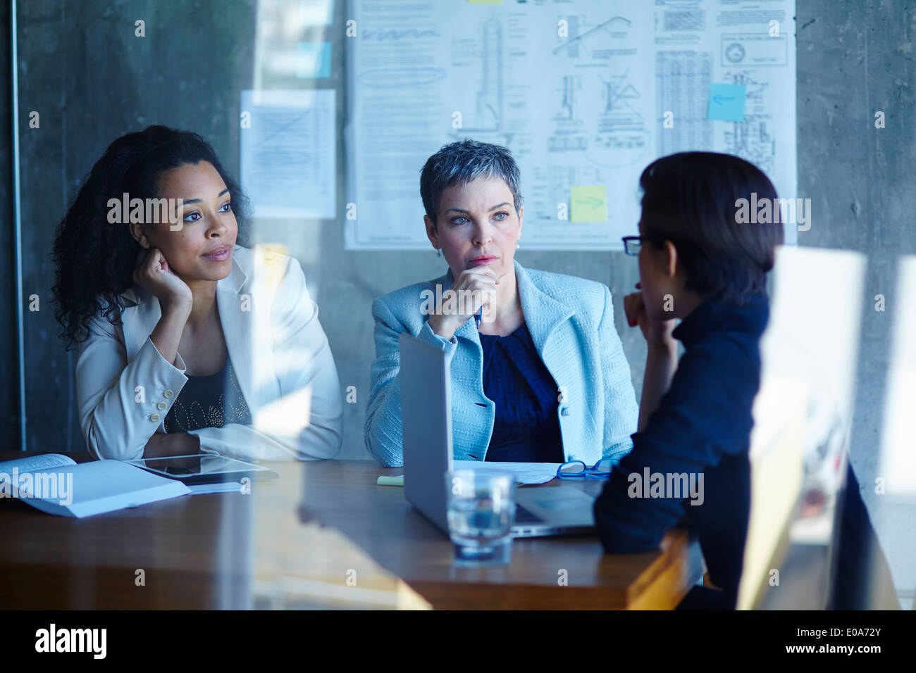 Three businesswomen discussing ideas in boardroom Stock Photo