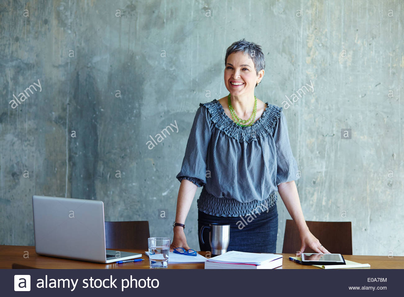 Portrait of mature businesswoman at conference table - Stock Image
