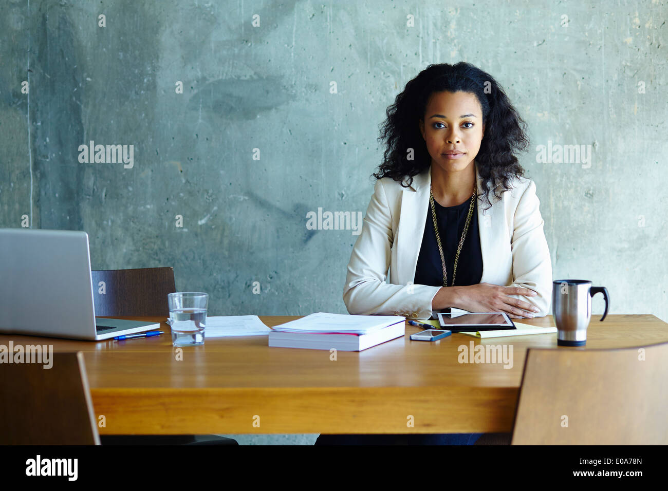 Portrait of young businesswoman at conference table - Stock Image