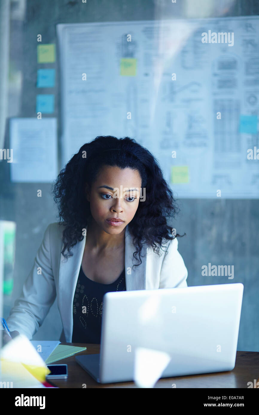 Young businesswomen working on laptop in office - Stock Image