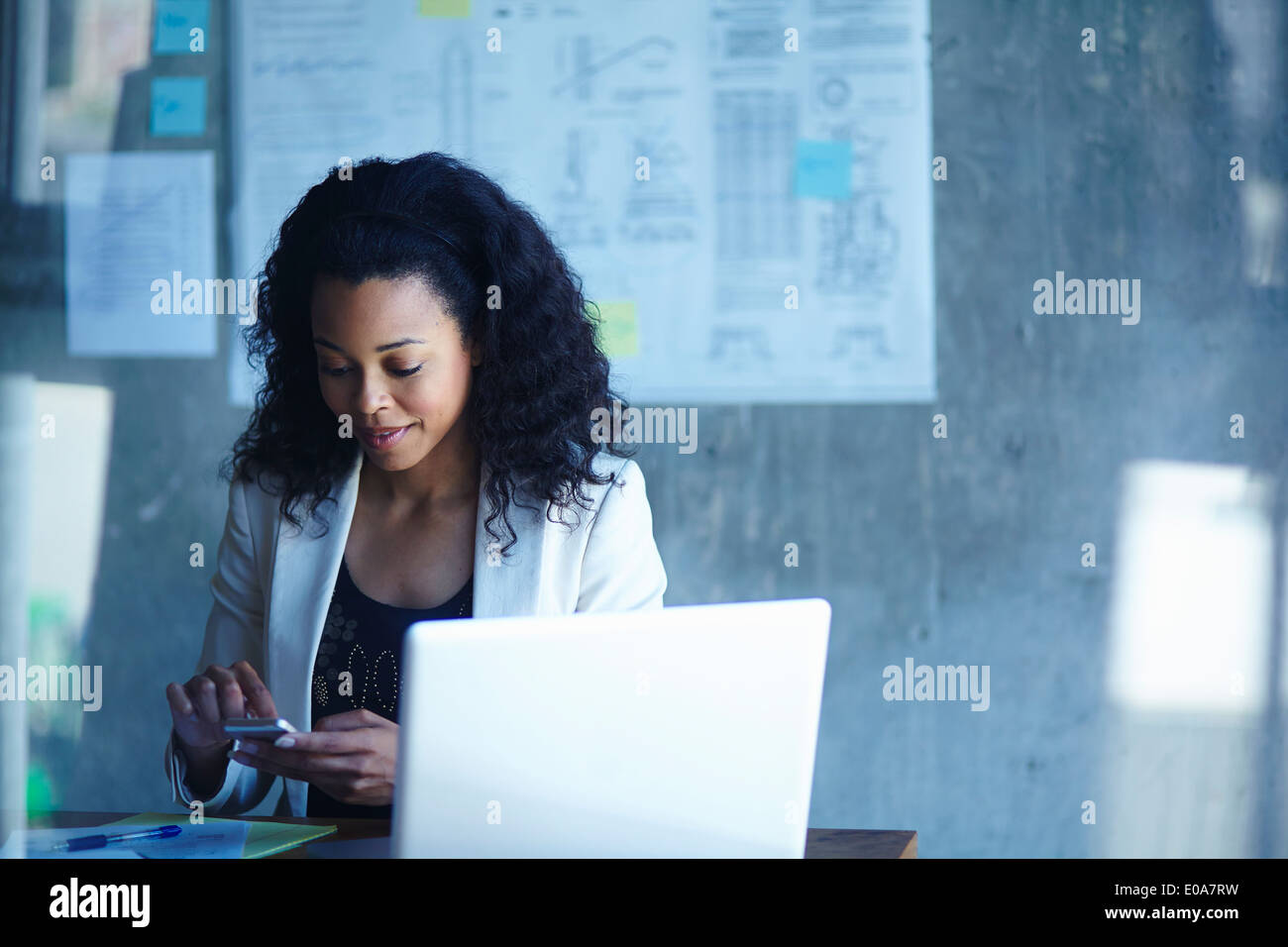 Young businesswomen texting on smartphone in office - Stock Image