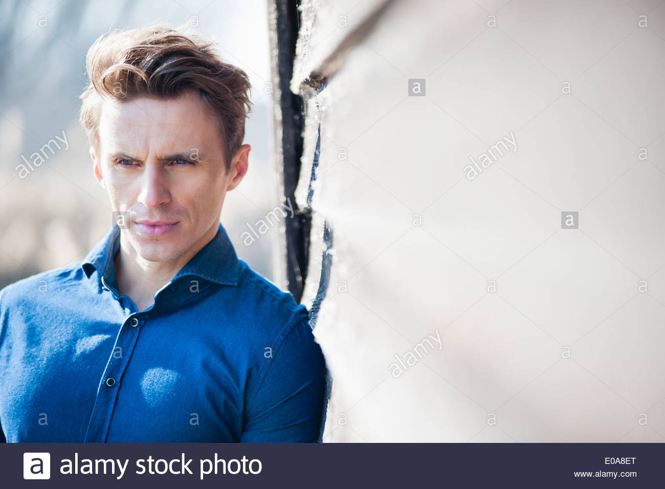 Mid adult man leaning against wall Stock Photo