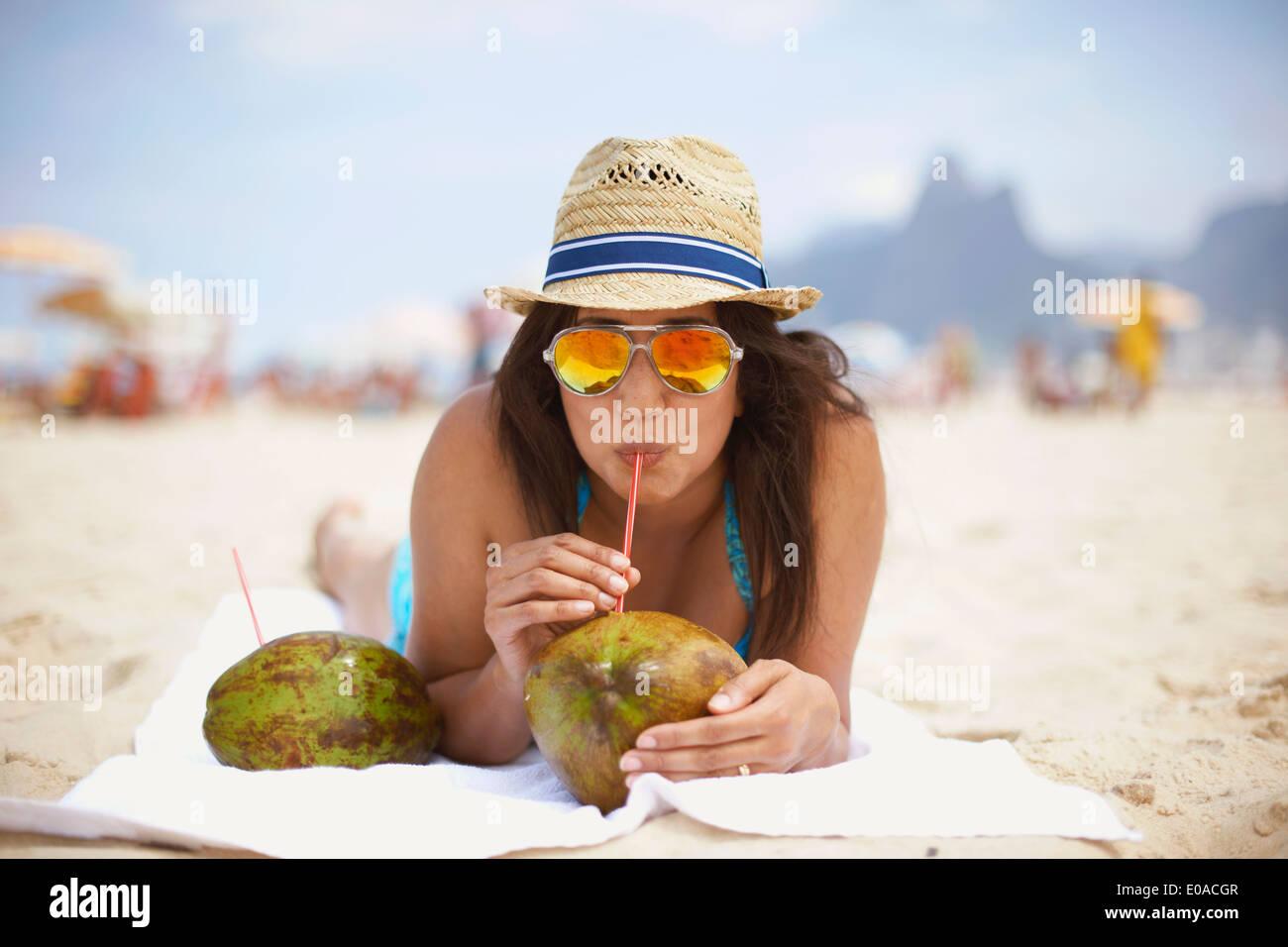 Portrait of mature woman drinking from coconut, Ipanema beach, Rio De Janeiro, Brazil - Stock Image