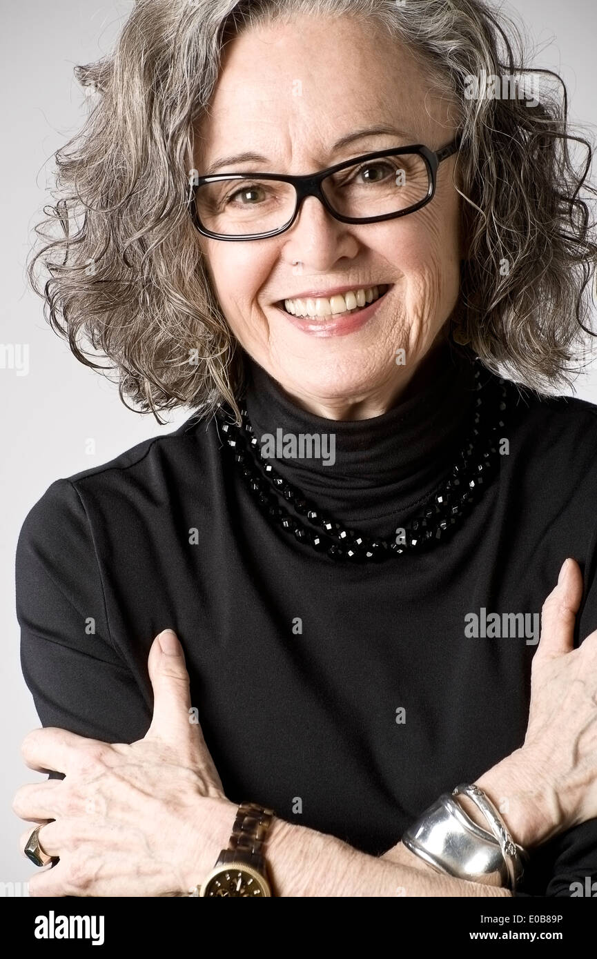 Portrait of senior woman, arms folded - Stock Image