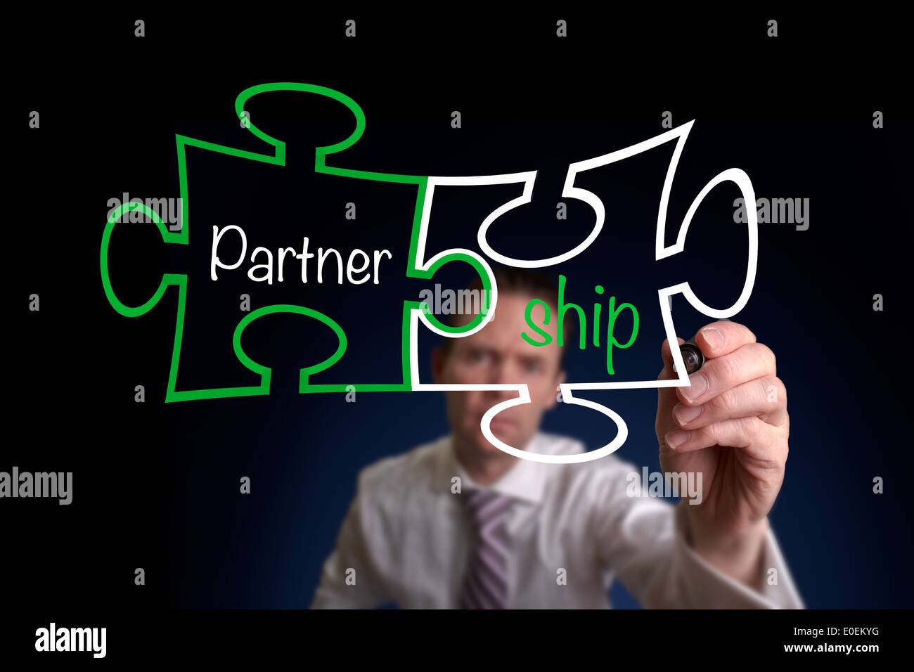 A businessman drawing a Partnership Puzzle Concept. - Stock Image