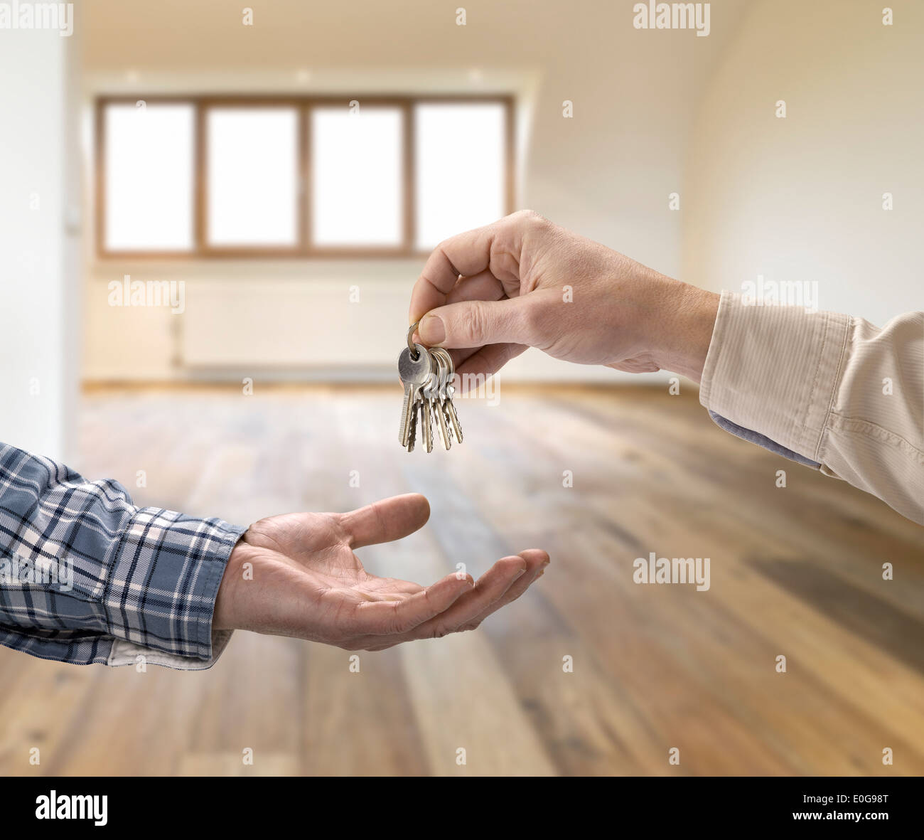 Realtor giving house key to buyer in empty room - Stock Image