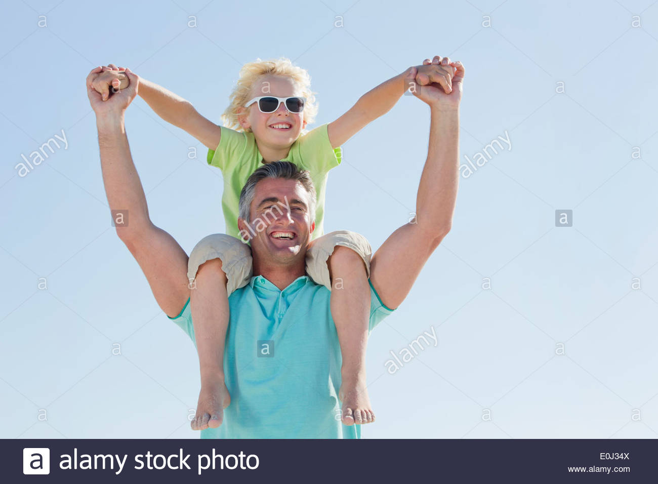 Happy father carrying son on shoulders - Stock Image