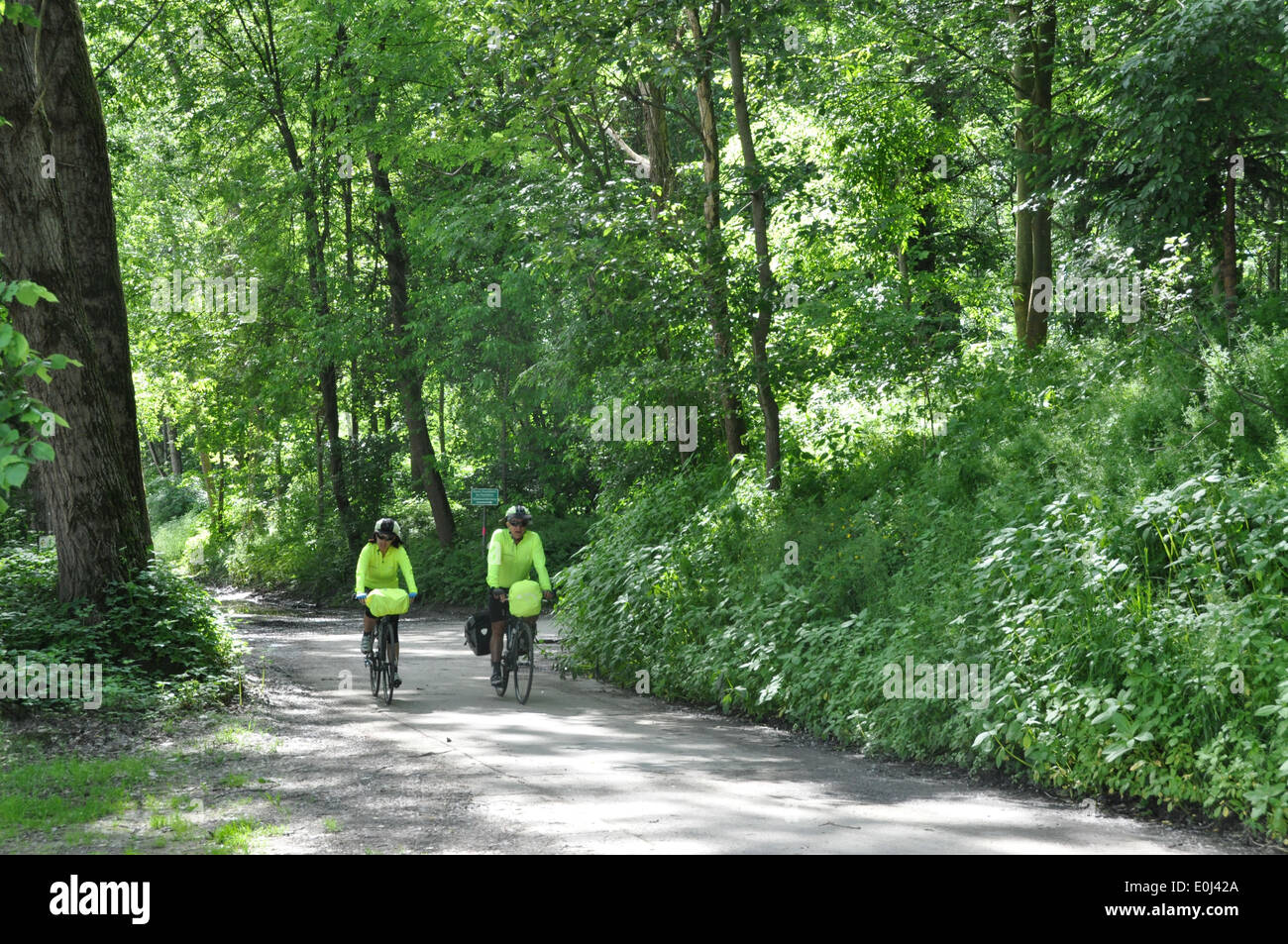 two-australian-cyclists-riding-their-bikes-in-a-natural-park-along-E0J42A.jpg