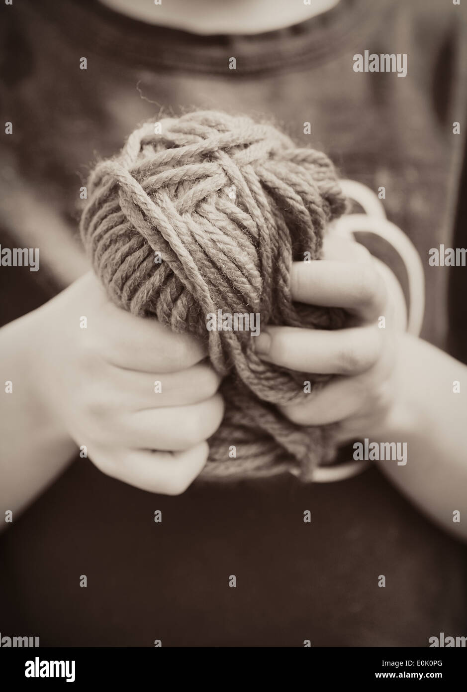 Close up of little girl holding a ball of yarn in her hands - Stock Image
