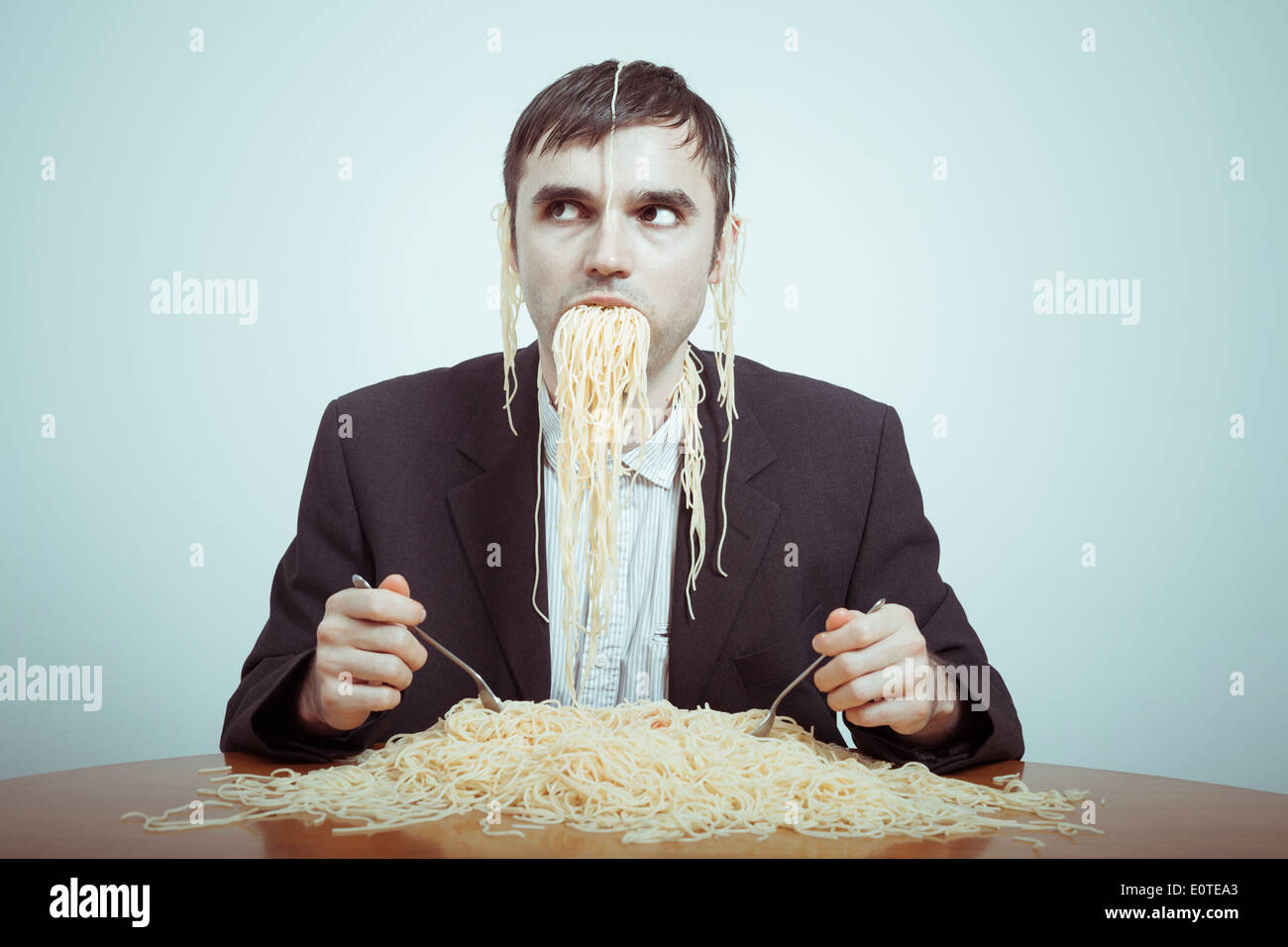 Overeating and consumerism concept. Silly nasty businessman eating pasta. - Stock Image