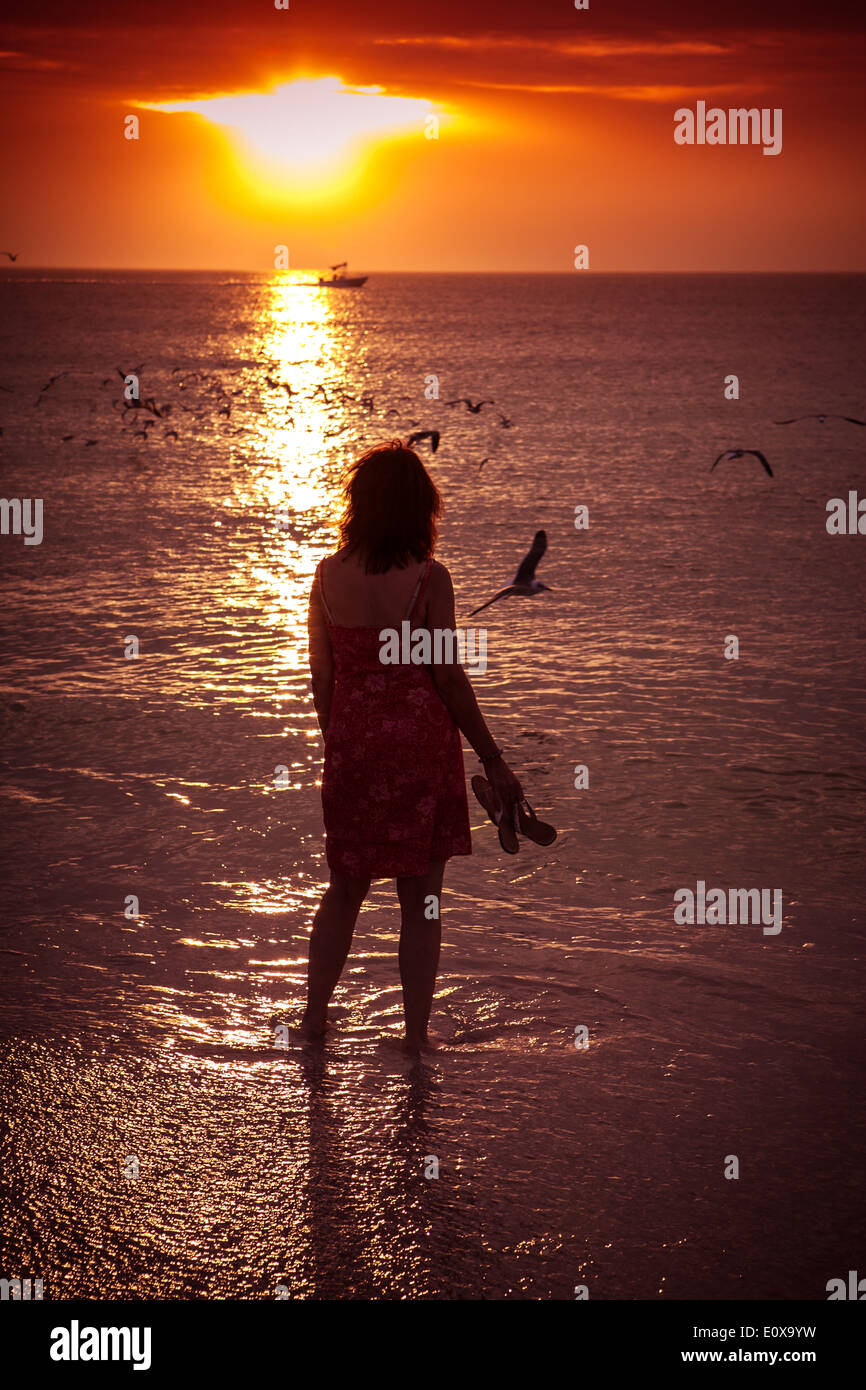 Woman alone on a beach at sunset - Stock Image