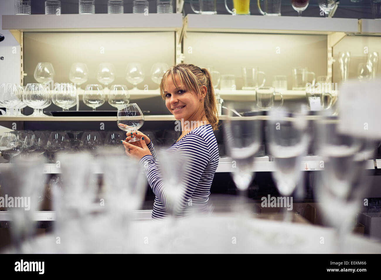 young hispanic woman shopping for furniture, glasses, dishes and home decor in store - Stock Image