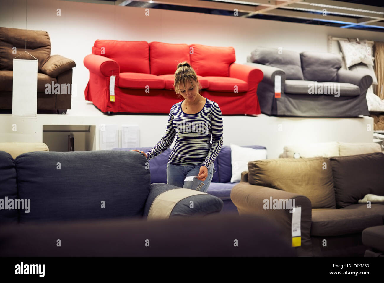 young hispanic woman shopping for furniture, sofa and home decor in store - Stock Image