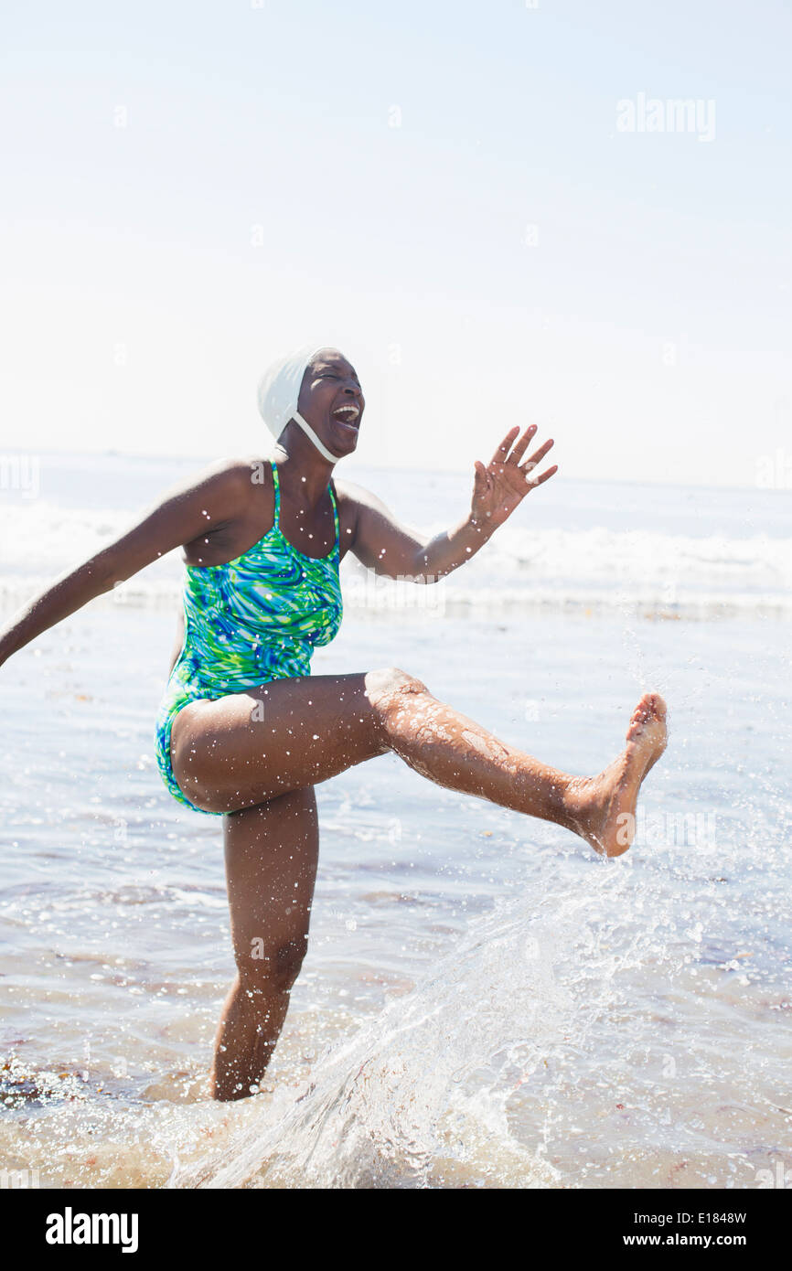 Woman splashing in ocean surf - Stock Image