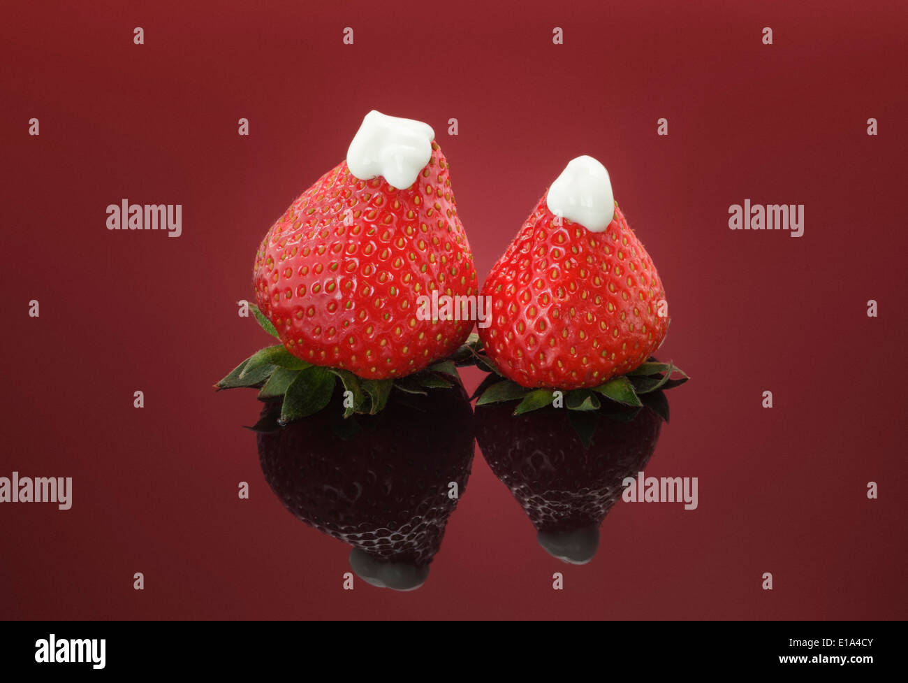 Two fresh Strawberries topped with natural thick Yogurt on red background - Stock Image
