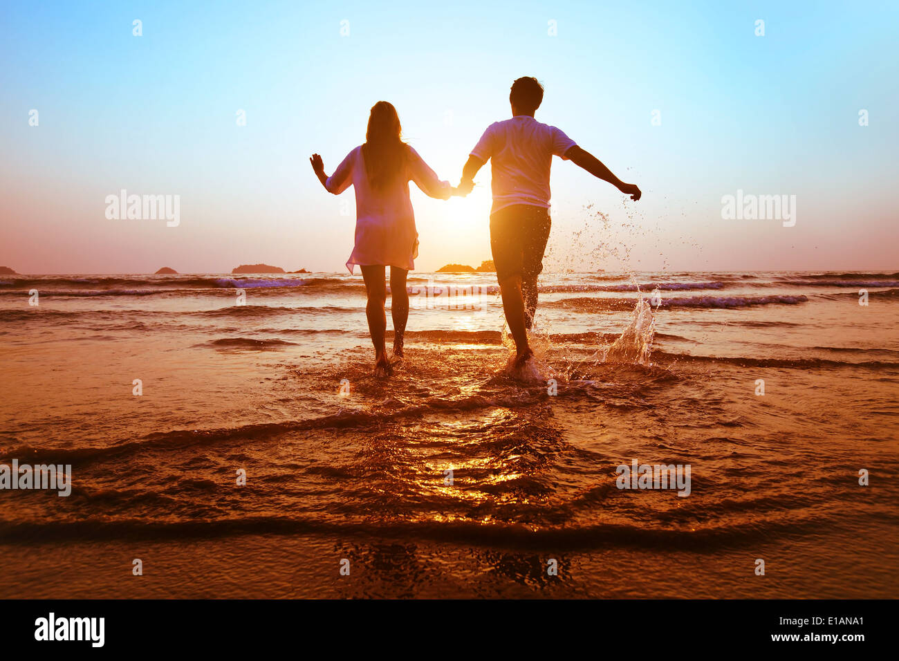 young happy couple running to the sea at sunset beach - Stock Image
