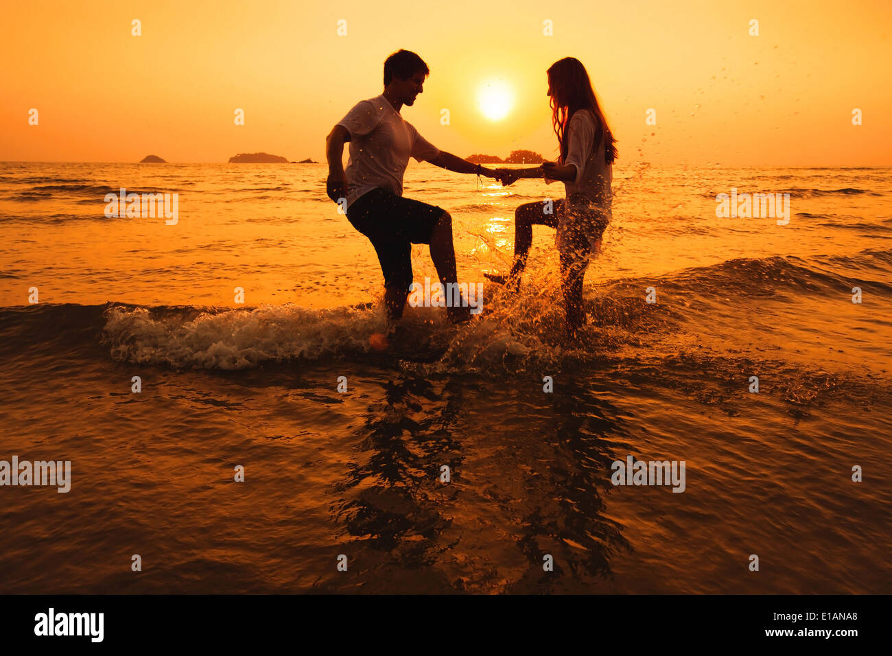 couple having fun in the sea at sunset beach - Stock Image