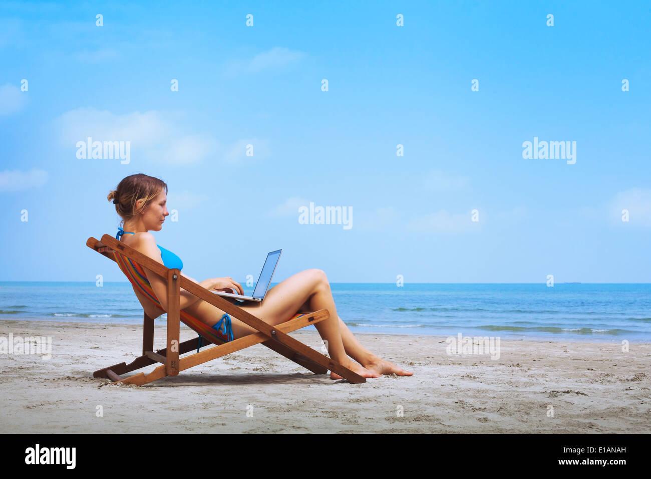 woman in bikini sitting with laptop on the beach - Stock Image