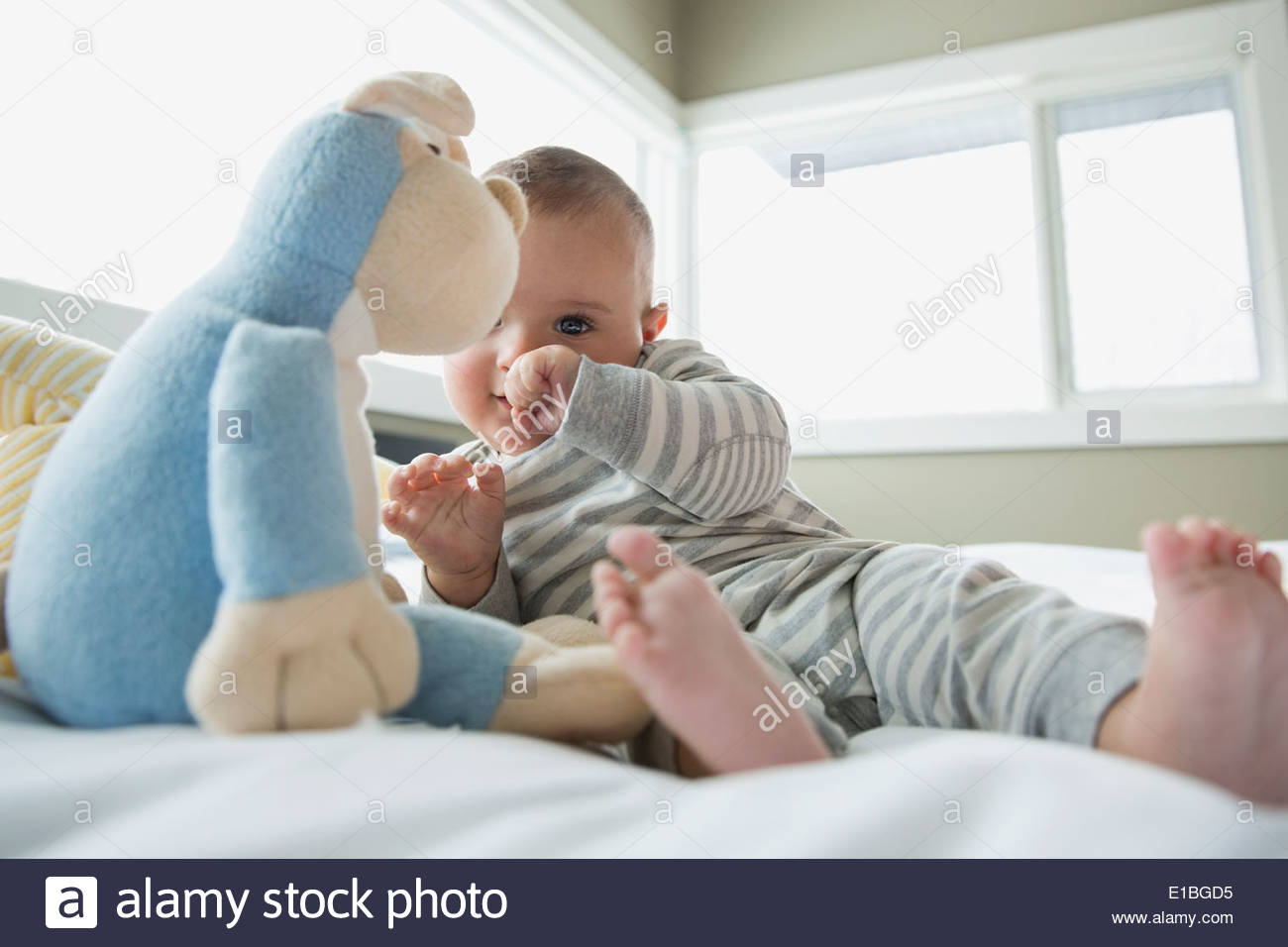 Baby with stuffed animal on bed - Stock Image