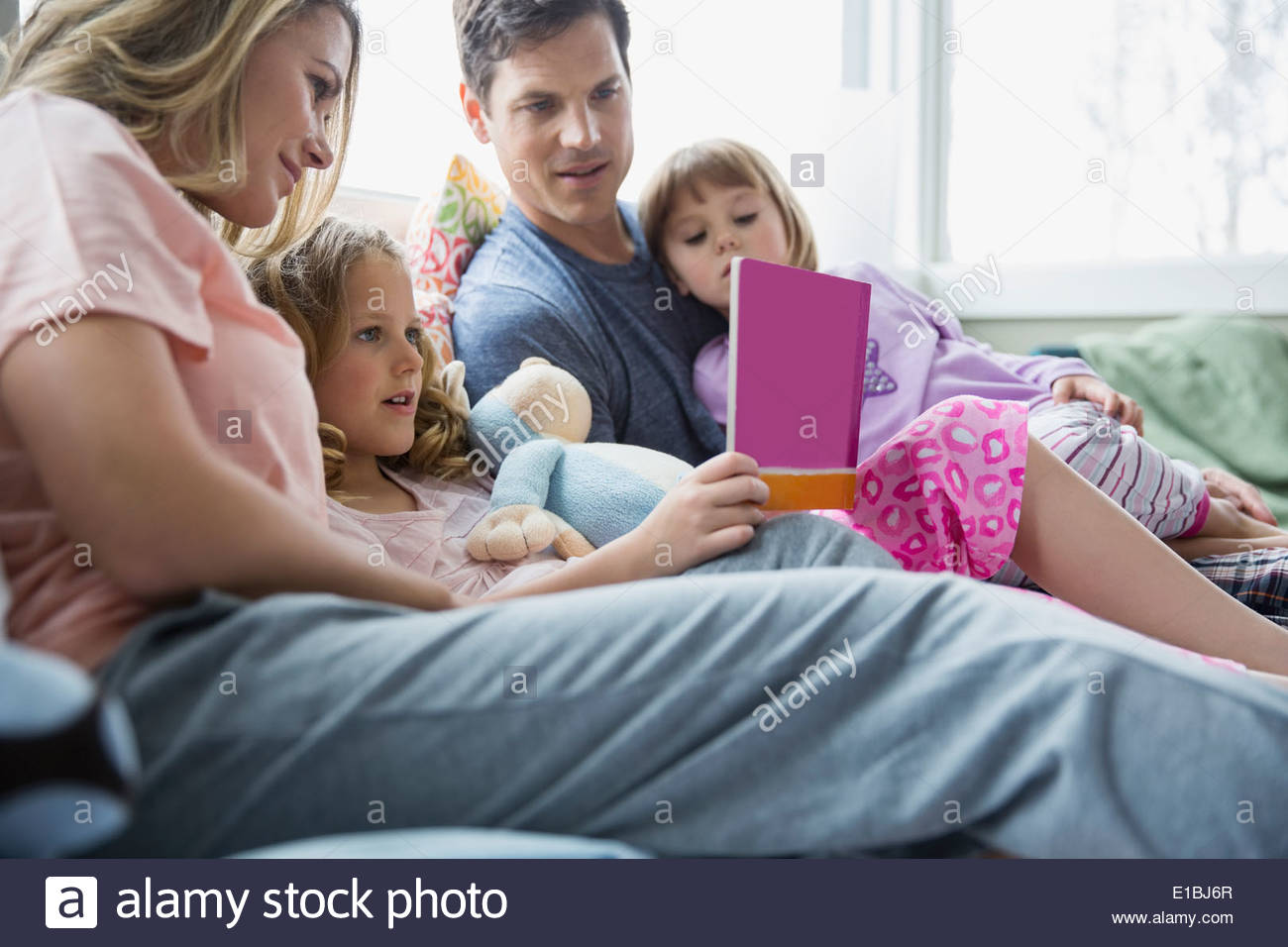 Family reading book on bed - Stock Image