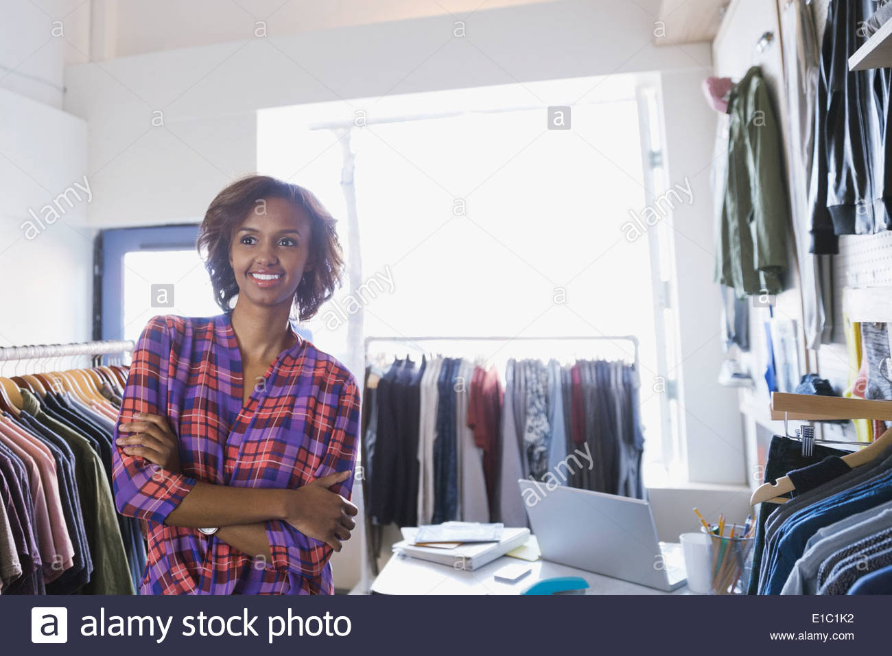 Confident business owner in clothing shop - Stock Image