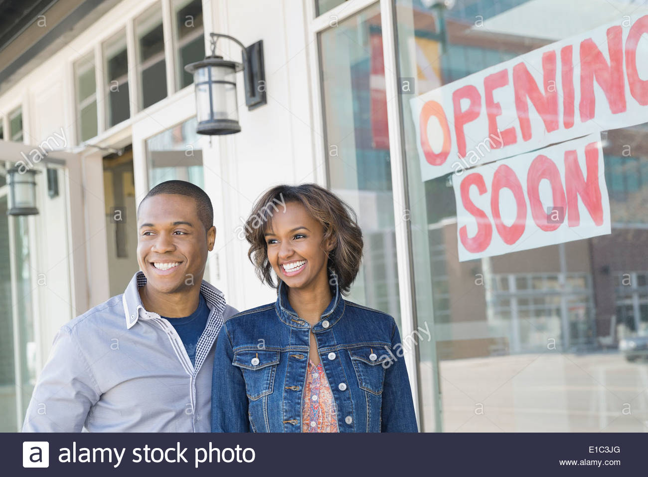 Portrait of business owners standing at new storefront - Stock Image