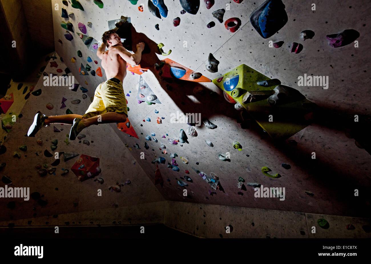 Man bouldering at indoor climbing centre - Stock Image