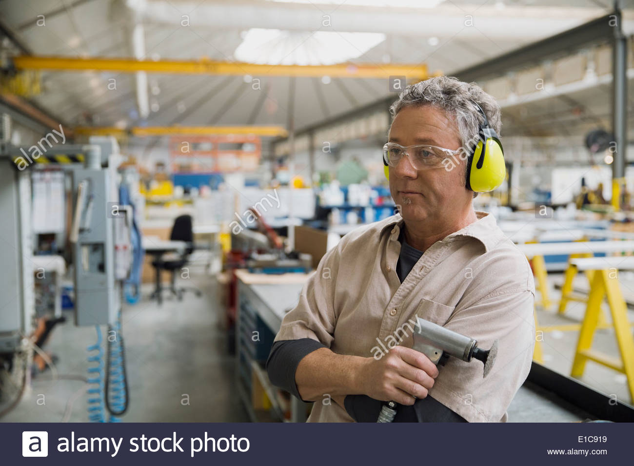 Worker with power sander in manufacturing plant - Stock Image