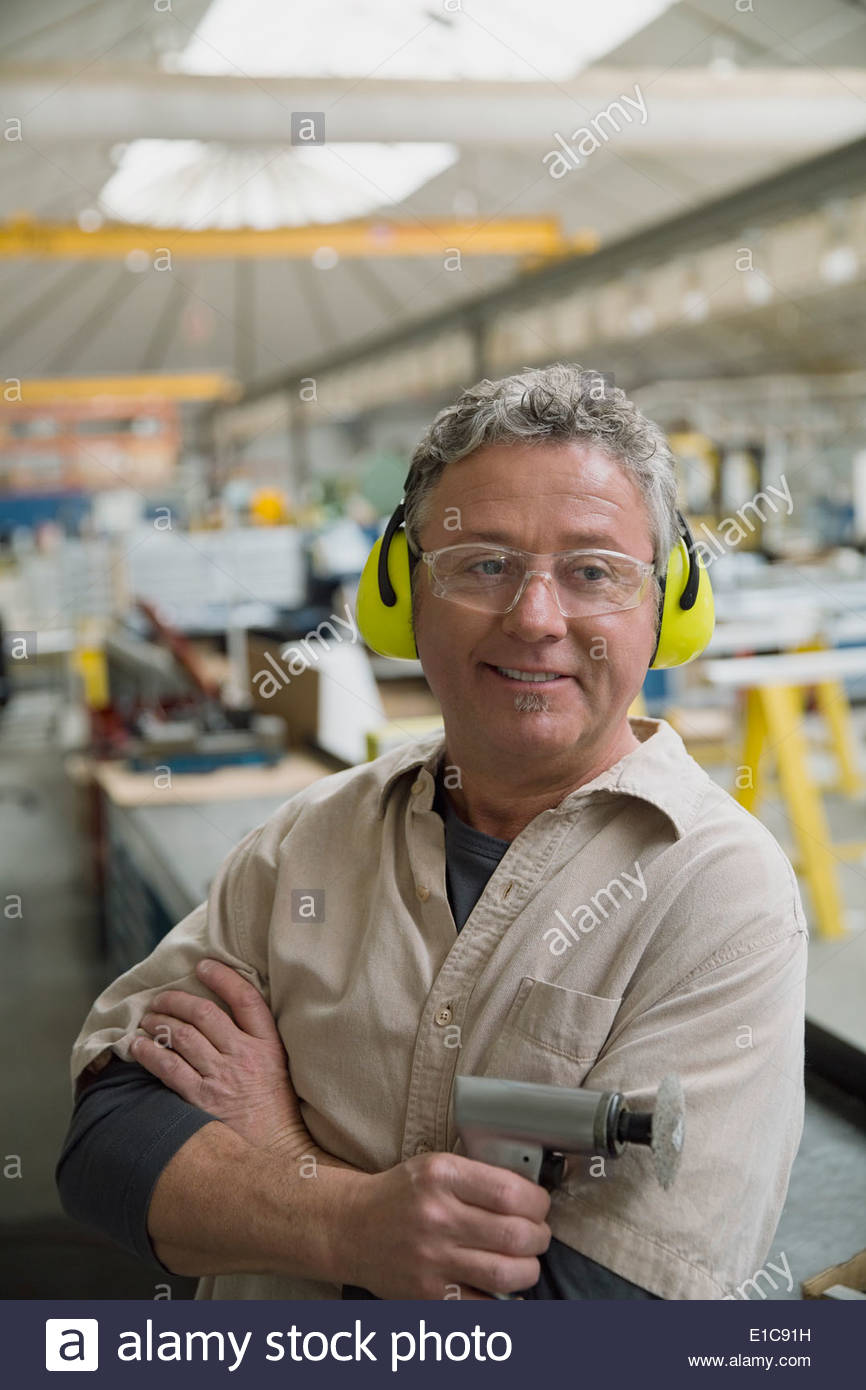 Confident worker with power sander in manufacturing plant - Stock Image