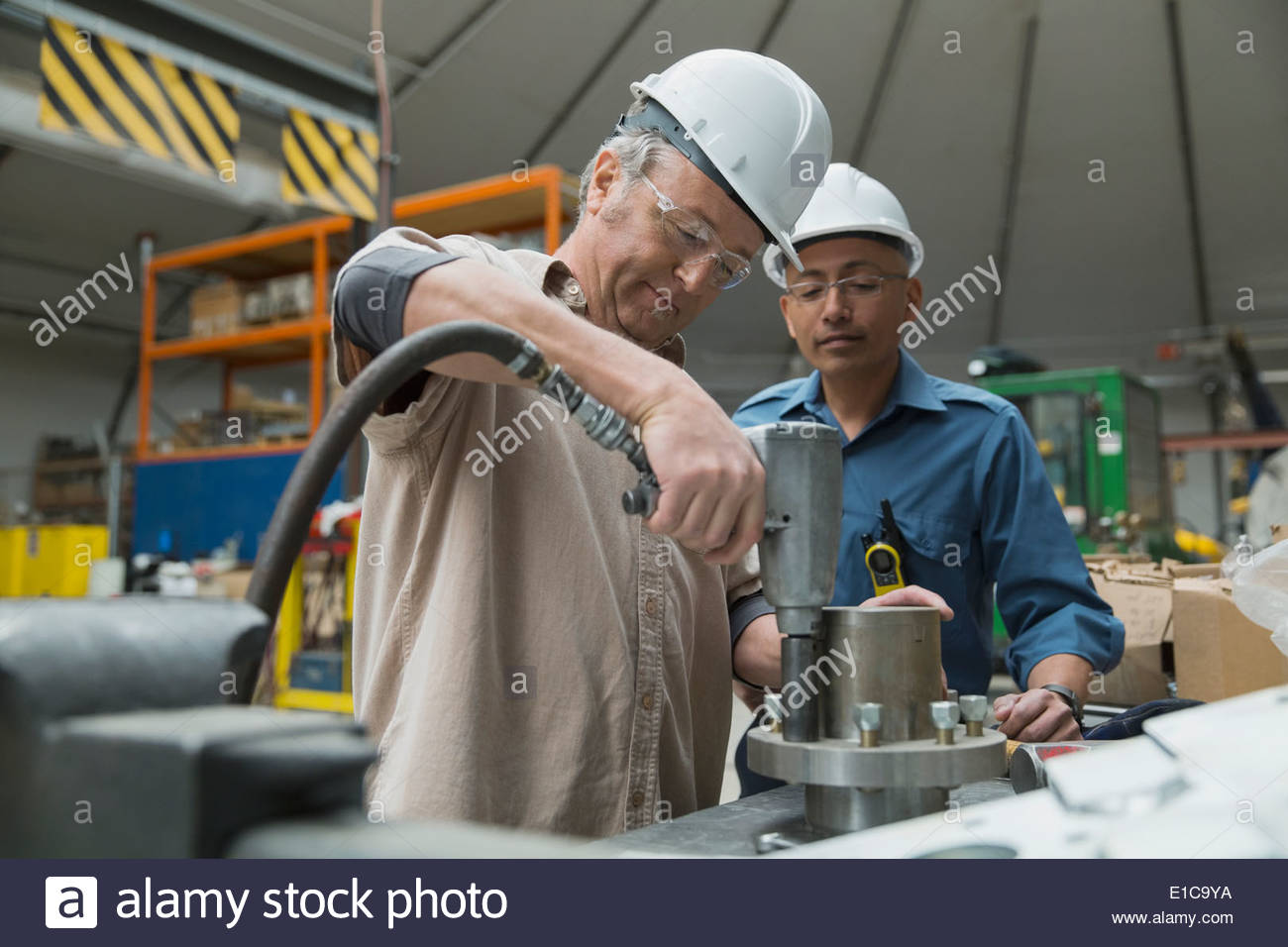 Workers using power drill in manufacturing plant - Stock Image