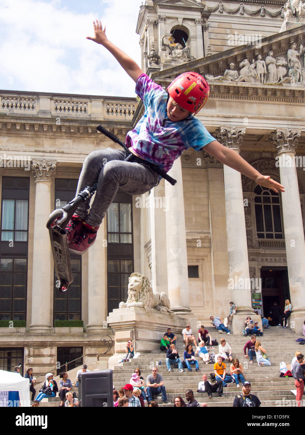 a-young-ten-year-old-scooter-rider-performs-an-aerial-stunt-in-front-E1D5FX.jpg