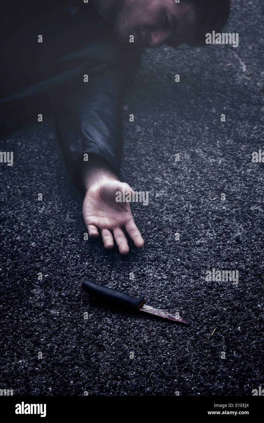 a man reaching out for a knife - Stock Image