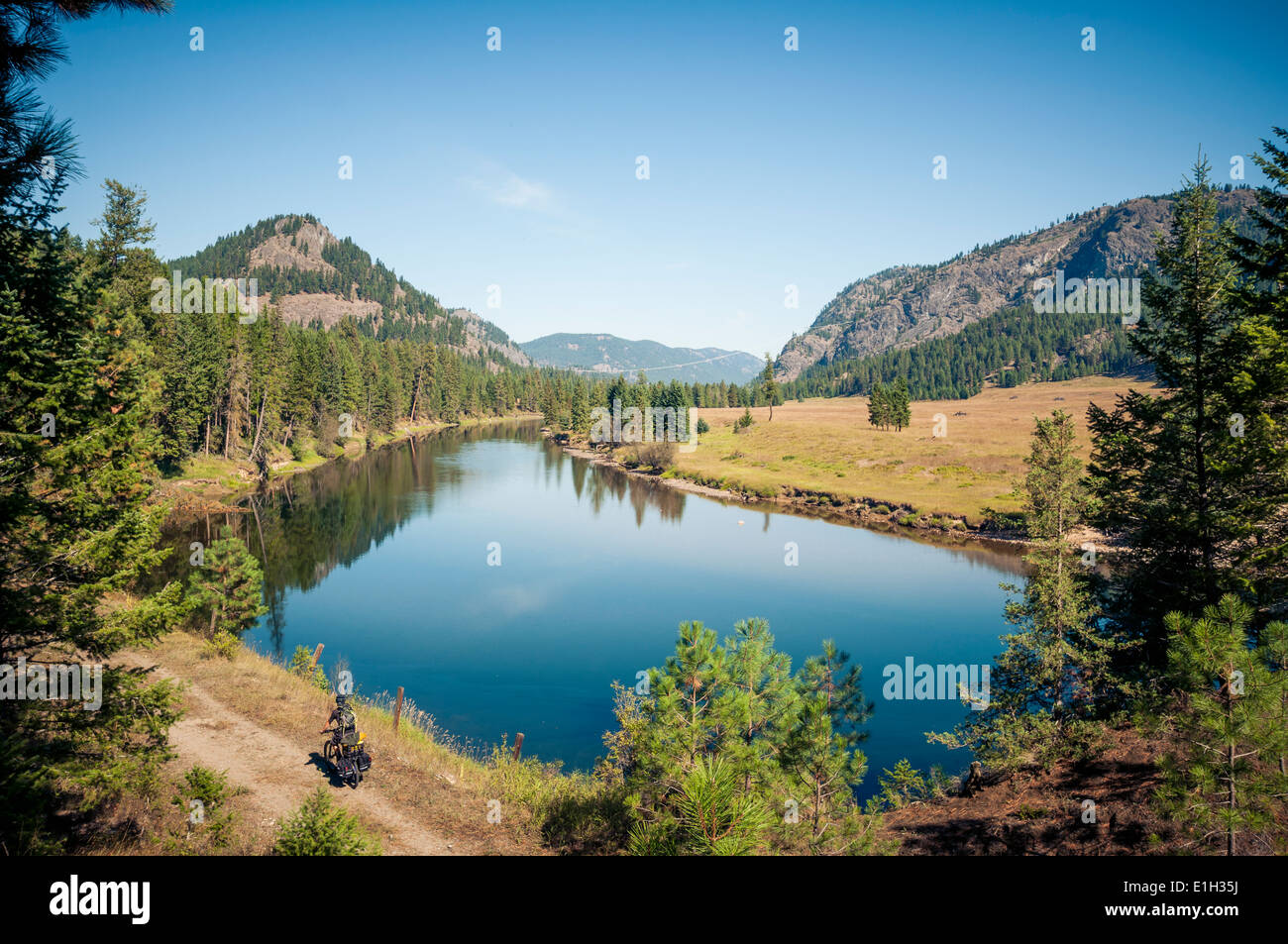 Male cyclist in Kettle Valley Rail-Trail/Kettle Valley Railway/KVR Trail next the Kettle Valley River, British Columbia, - Stock Image