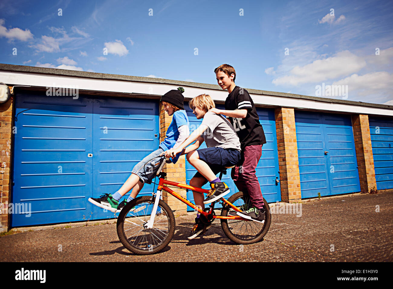 Boy giving two friends a ride on bike Stock Photo