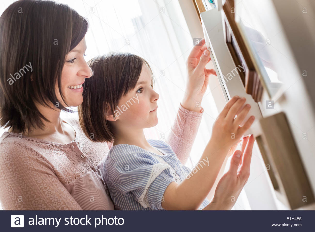 Mother and daughter adjusting picture - Stock Image
