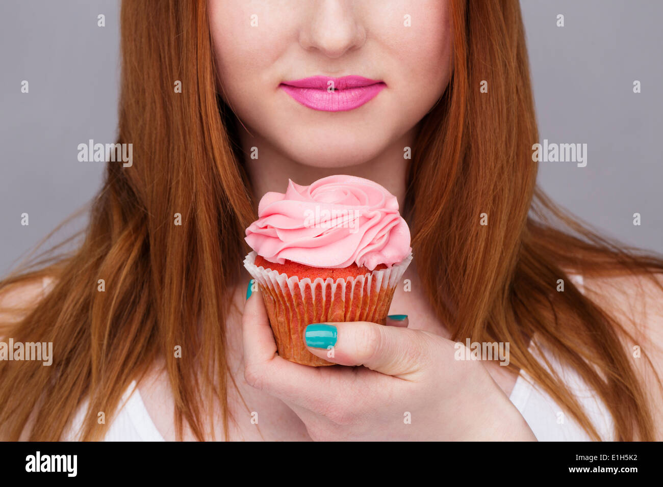 Cropped image of young woman holding cupcake - Stock Image