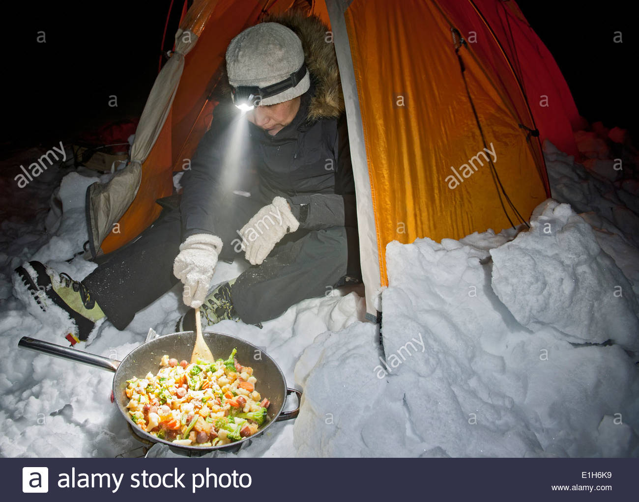 Mature woman cooking outside tent at night, Langjokull glacier, South Iceland - Stock Image