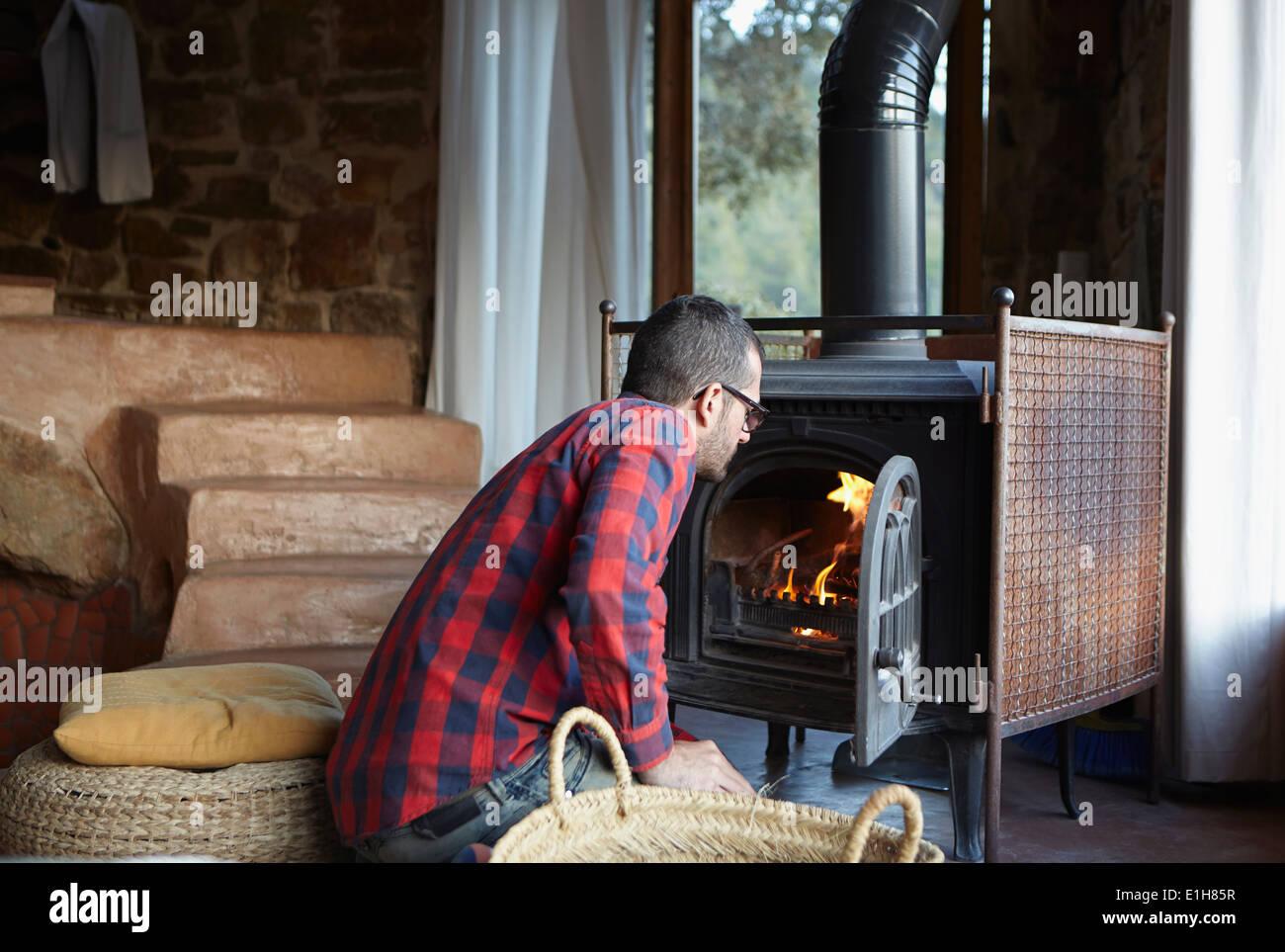 Mid adult man watching log burning fire - Stock Image