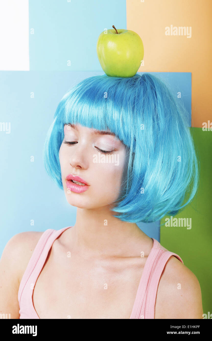 Bizarre Stylized Woman in Blue Wig with Green Apple - Stock Image