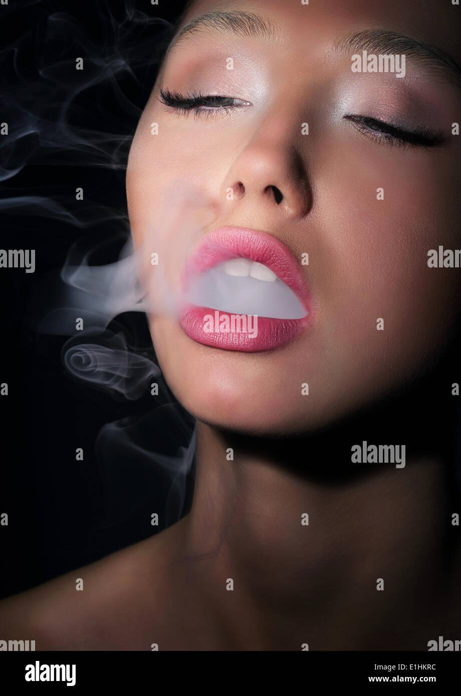 Dependence. Addiction. Woman Smoker Exhales Smoke of Cigarette - Stock Image