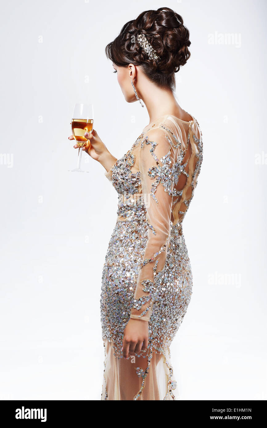 Elegant Woman in Silver-Golden Dress holding Wineglass of Champagne. Luxury - Stock Image