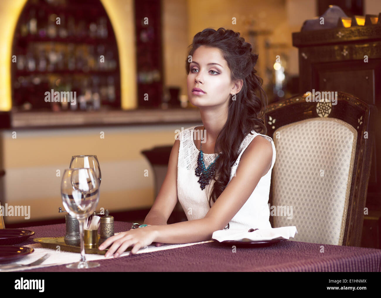 Dating. Dreaming Woman waiting at Decorated Table in Restaurant Interior - Stock Image
